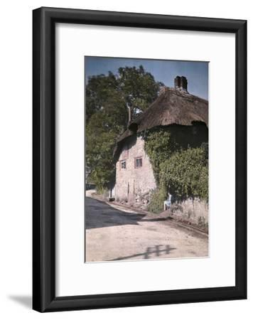 A Girl Sits on a Wall Next to an Old Thatched Cottage-Clifton R^ Adams-Framed Photographic Print