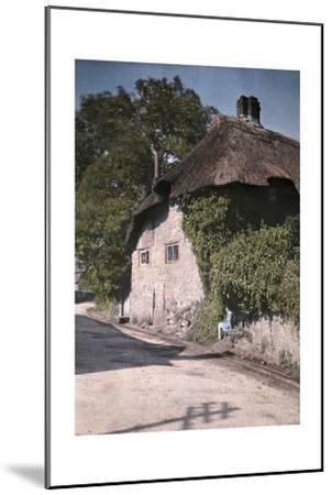 A Girl Sits on a Wall Next to an Old Thatched Cottage-Clifton R^ Adams-Mounted Photographic Print