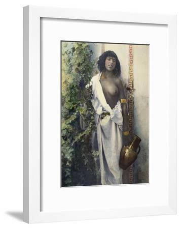 A Bedouin Woman Half Draped in White Cloth Stands Holding an Urn--Framed Photographic Print