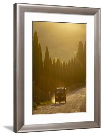 A Three Wheeled Van Drives Up a Dirt Road Lines with Cypress Trees-Tino Soriano-Framed Photographic Print