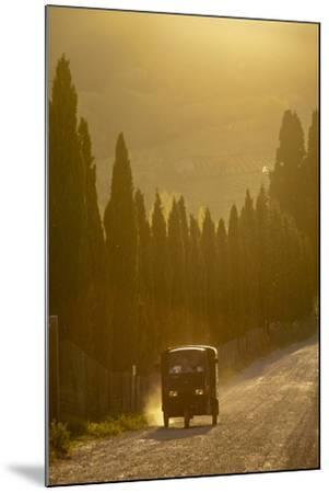 A Three Wheeled Van Drives Up a Dirt Road Lines with Cypress Trees-Tino Soriano-Mounted Photographic Print