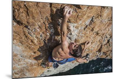 A Climber, Without Ropes, Scales a Cliff Rising from the Gulf of Oman-Jimmy Chin-Mounted Photographic Print