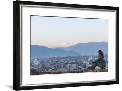 A Woman Sits on a Rooftop in Kathmandu and with the Ganesh Himal Mountain Range in the Distance-Alex Treadway-Framed Photographic Print