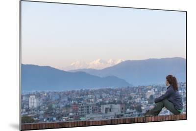 A Woman Sits on a Rooftop in Kathmandu and with the Ganesh Himal Mountain Range in the Distance-Alex Treadway-Mounted Photographic Print