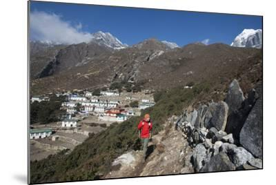 A Hiker Walks Past a Wall of Mani Stones Inscribed with an Ancient Tibetan Mantra-Alex Treadway-Mounted Photographic Print