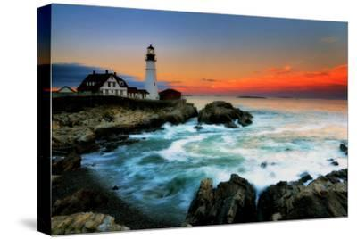 The Sun Setting Behind the Portland Head Light as Waves Surge onto the Rocky Shore-Robbie George-Stretched Canvas Print