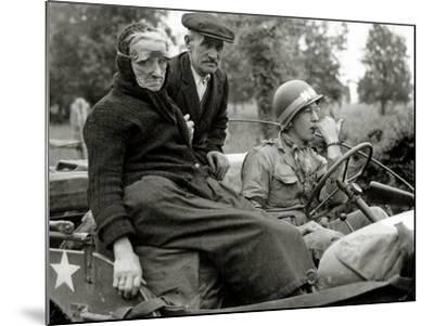 An Elderly Couple Sitting in a Jeep Driven by a Military Police--Mounted Photographic Print