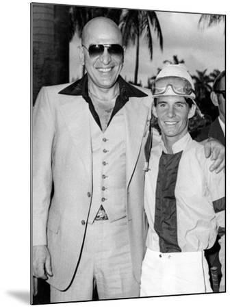 Actor Telly Savalas Poses with a Jockey at Hialeah Park, C.1970--Mounted Photographic Print