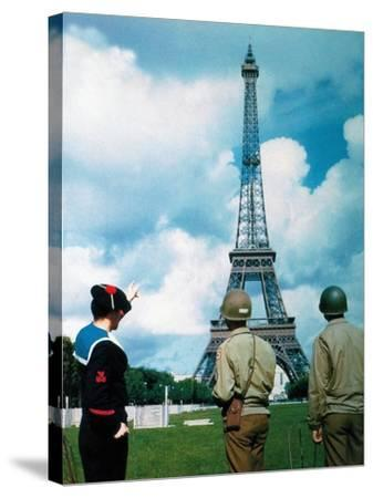 A French Sailor and Two Gis from Army Service Forces Looking at the Eiffel Tower--Stretched Canvas Print