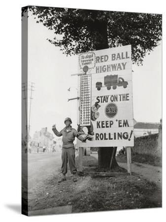 """A Gi Standing Next to a Sign Saying """"Red Ball Highway""""--Stretched Canvas Print"""