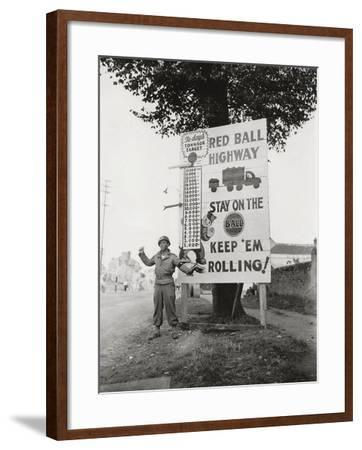 """A Gi Standing Next to a Sign Saying """"Red Ball Highway""""--Framed Photographic Print"""