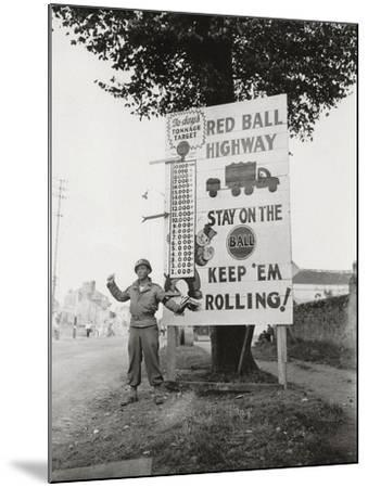 """A Gi Standing Next to a Sign Saying """"Red Ball Highway""""--Mounted Photographic Print"""