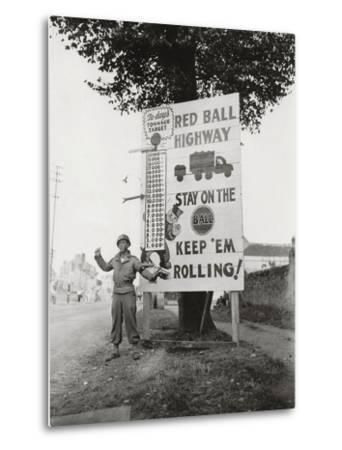 """A Gi Standing Next to a Sign Saying """"Red Ball Highway""""--Metal Print"""