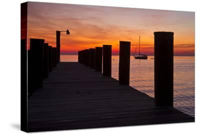 Sunrise on the Water with an Empty Dock and a Sailboat in the Distance of Tilghman Island, Maryland-Karine Aigner-Stretched Canvas Print