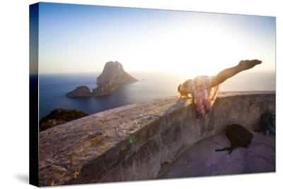 A Young Woman Does an Acrobatic Yoga Pose at the Torre Des Savinar Lookout Tower in Sw Ibiza-Day's Edge Productions-Stretched Canvas Print