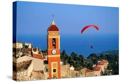 Paraglider Soaring past Tower of Colourful Village Church, Alpes-Maritimes, Roquebrune, Provence-Al-David Tomlinson-Stretched Canvas Print