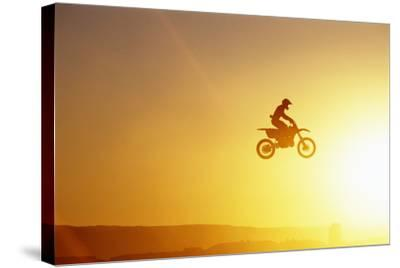Silhouette of Motocross Race in mid Air, Sunset, Side View-John P Kelly-Stretched Canvas Print