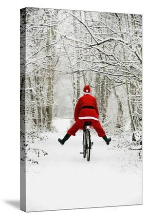 Father Christmas Riding Bicycle in Snowy Woodland Path--Stretched Canvas Print