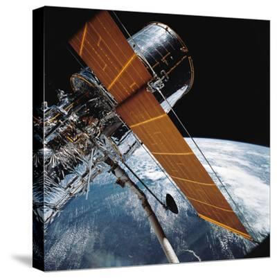 The Hubble Space Telescope Backdropped by Planet Earth--Stretched Canvas Print