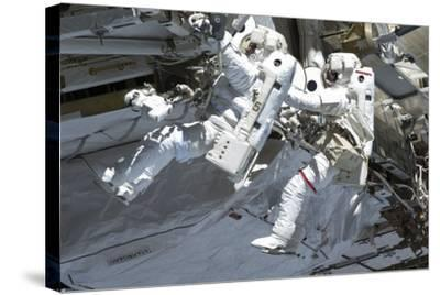 Astronauts Participate in a Spacewalk on the International Space Station--Stretched Canvas Print