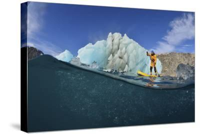 Stand Up Paddle Boarding by an Iceberg, in a Fjord in Southeast Greenland-Keith Ladzinski-Stretched Canvas Print
