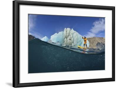 Stand Up Paddle Boarding by an Iceberg, in a Fjord in Southeast Greenland-Keith Ladzinski-Framed Photographic Print