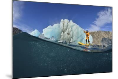 Stand Up Paddle Boarding by an Iceberg, in a Fjord in Southeast Greenland-Keith Ladzinski-Mounted Photographic Print