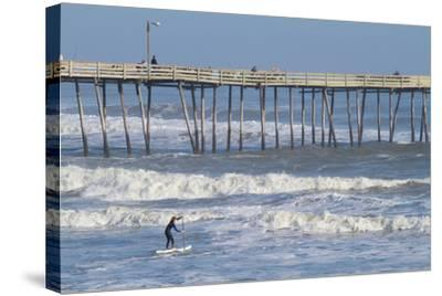 A Boy Paddles Out into Big Waves on His Standup Paddle Board Next to Nags Head Pier-Skip Brown-Stretched Canvas Print