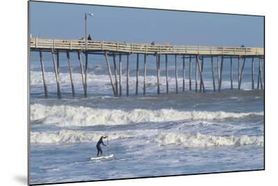 A Boy Paddles Out into Big Waves on His Standup Paddle Board Next to Nags Head Pier-Skip Brown-Mounted Photographic Print