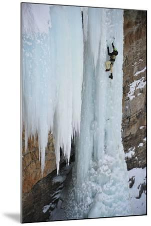 A Man Ice-Climbing the Fang, an Ice Formation on the Side of a Cliff-Keith Ladzinski-Mounted Photographic Print