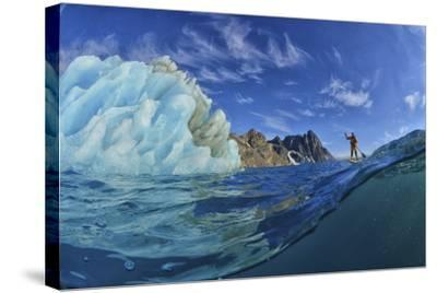 A Person Stand Up Paddle Boarding Near an Iceberg in the Fjords of Southeast Greenland-Keith Ladzinski-Stretched Canvas Print