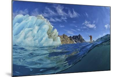 A Person Stand Up Paddle Boarding Near an Iceberg in the Fjords of Southeast Greenland-Keith Ladzinski-Mounted Photographic Print