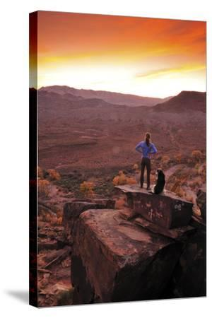 A Woman and a Dog on Top of a Rock Covered in Petroglyphs, Looking at a Beautiful Sunset-Keith Ladzinski-Stretched Canvas Print