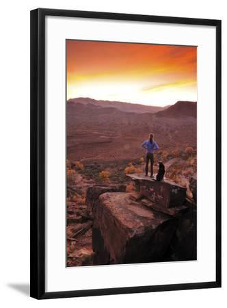 A Woman and a Dog on Top of a Rock Covered in Petroglyphs, Looking at a Beautiful Sunset-Keith Ladzinski-Framed Photographic Print