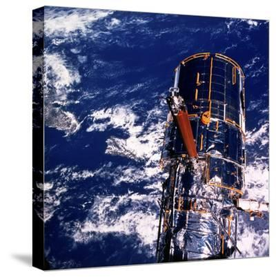 Hubble Space Telescope Above the Earth--Stretched Canvas Print