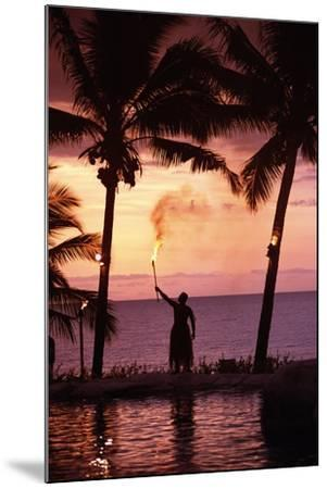 Native in a Grass Skirt Holding a Flaming Torch by Coast at Sunset-Design Pics Inc-Mounted Photographic Print
