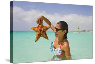 A Woman Holds Up a Starfish She Found in the Shallow Water Off of a Beach-Mike Theiss-Stretched Canvas Print