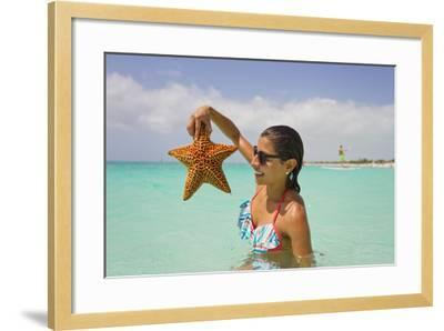 A Woman Holds Up a Starfish She Found in the Shallow Water Off of a Beach-Mike Theiss-Framed Photographic Print
