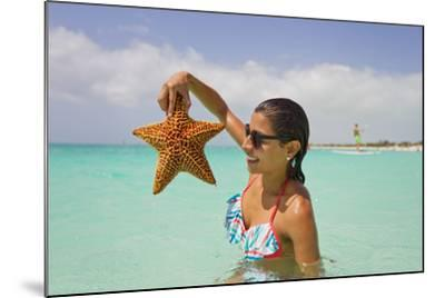 A Woman Holds Up a Starfish She Found in the Shallow Water Off of a Beach-Mike Theiss-Mounted Photographic Print
