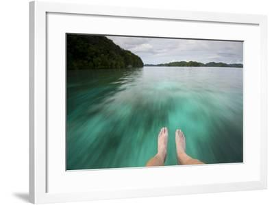Feet Dangle over the Bow of an Unseen Boat as it Speeds over the Water-Michael Melford-Framed Photographic Print