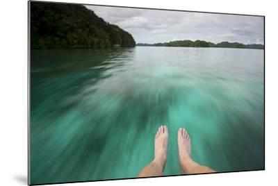 Feet Dangle over the Bow of an Unseen Boat as it Speeds over the Water-Michael Melford-Mounted Photographic Print