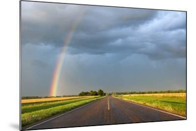 A Thunderstorm Produces a Vivid Rainbow Next to a Rain-Soaked Paved Road-Jim Reed-Mounted Photographic Print