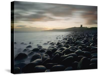 Looking Along Boulder Covered Beach Towards Dunstanburgh Castle at Dawn-Design Pics Inc-Stretched Canvas Print