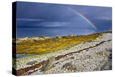 Rainbow Above Rocky Beach and Small Boat--Stretched Canvas Print