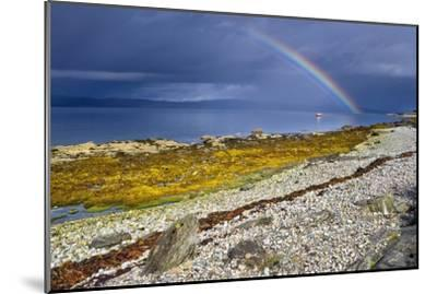 Rainbow Above Rocky Beach and Small Boat--Mounted Photographic Print