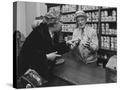 A Replica of an Early General Store Depicting a Salesman with a Can of Pears in Hand as He Tells a --Stretched Canvas Print