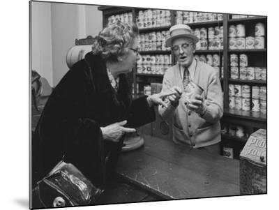 A Replica of an Early General Store Depicting a Salesman with a Can of Pears in Hand as He Tells a --Mounted Photographic Print