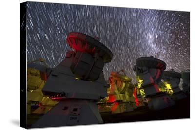A Time-Exposure Image of Star Trails over the Alma Radio Telescopes, 5000 Meters High in the Andes-Babak Tafreshi-Stretched Canvas Print