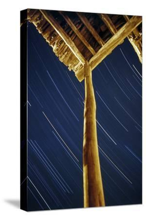 A Long Exposure of Sky Motion Shows Star Trails over the Wooden Roof of a Village House-Babak Tafreshi-Stretched Canvas Print