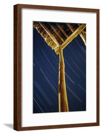 A Long Exposure of Sky Motion Shows Star Trails over the Wooden Roof of a Village House-Babak Tafreshi-Framed Photographic Print